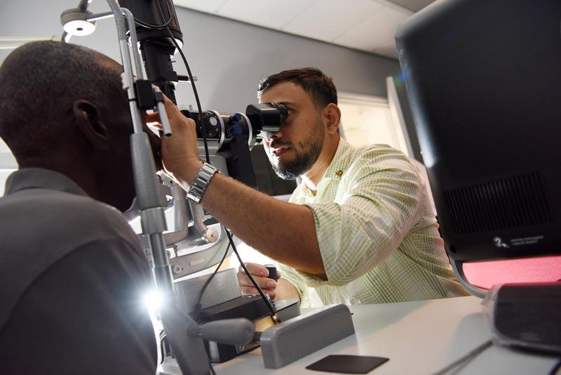 Dr. Shailendra Sugrim, of Guyana, examines glaucoma patient's eyes at Queen Elizabeth Hospital in Barbados, Photography: Geoff Bugbee, 2018.