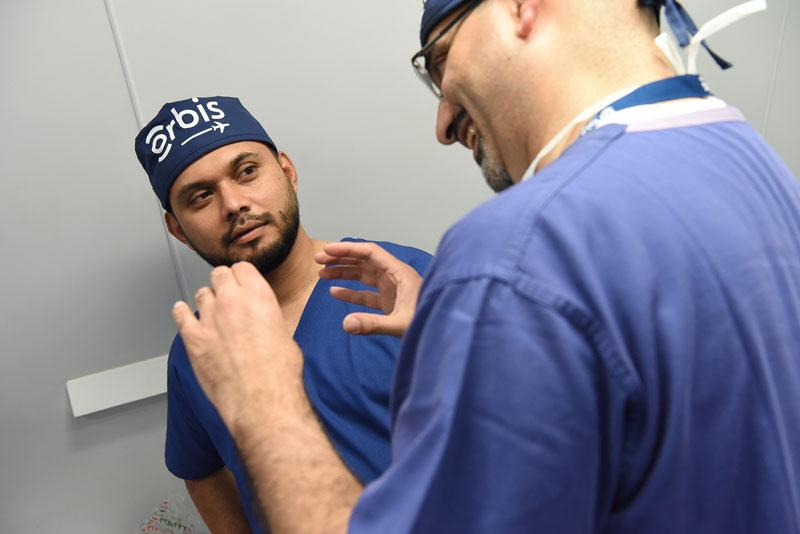 Dr. Shailendra Sugrim listens to post-surgical chalk-talk from Dr. Malik Kahook aboard the Orbis Flying Eye Hospital, Photography: Geoff Bugbee, 2018.