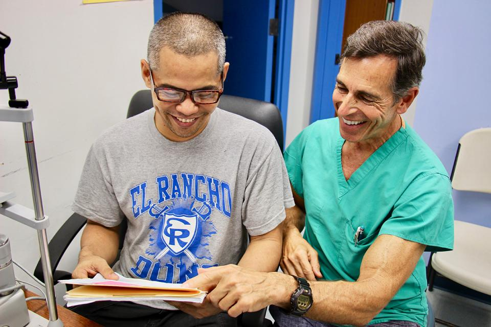 Dr. Rutgard helps a patient read for the first time in years with custom glasses. Image 2 of 10